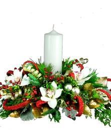 Holiday centerpiece of orchids, greenery, ornaments and a white pillar candle.