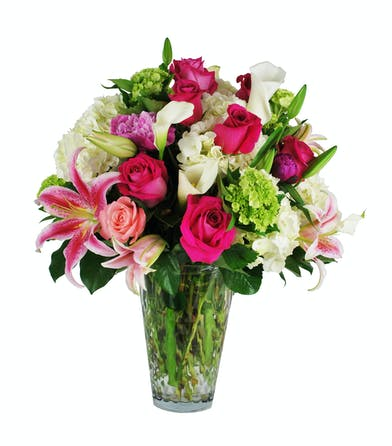 Bright luxury flowers in pinks and greens in a clear glass vase.