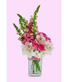 Orchids, roses, hydrangea and snap dragons in a clear glass vase accented with a blingy pink ribbon.