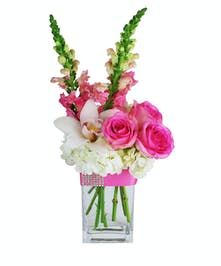 White and pink arrangement in a clear glass cube vase tied with pink blingy ribbon.