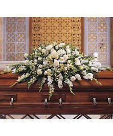 Casket spray of white carnations, gerberas, gladioli, asters, orchids, roses and stock, along with emerald palm and salal.