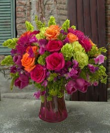 Pink, green and orange roses and Holland flowers in a red glass vase.