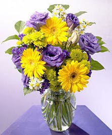 Yellow and purple flowers in a clear glass vase.