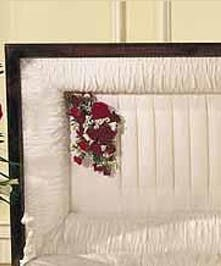 Casket pillow of red spray roses, mini carnations, white monte casino and a single red rose.