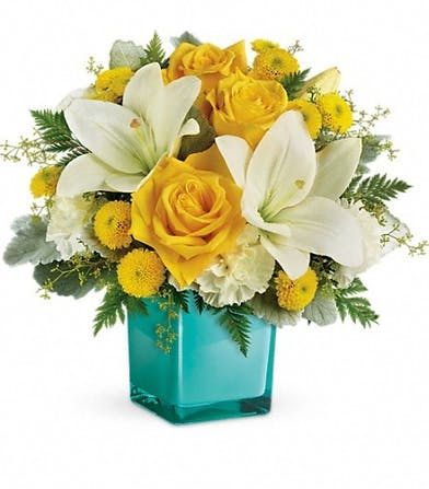 Golden roses and white lilies in an aqua cube vase.