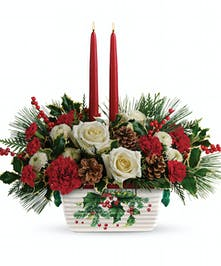Christmas centerpiece of roses and winter greenery arranged in a stoneware serving dish, with two red taper candles.