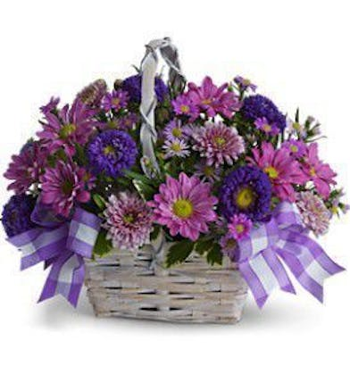 Flowers in shades of purple and blue in a white bamboo basket tied with lavender ribbon.