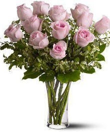 One dozen light pink roses and greenery arranged in a clear glass vase.