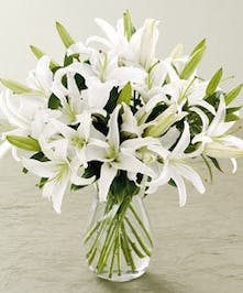 All-white bouquet of Casablanca lilies in a clear glass vase