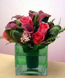Hand-tied bouquet of roses and calla lilies in a clear glass cube vase.