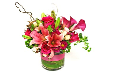 Asiatic lilies, calla lilies, roses, jap aster and assorted greenery with a bird's nest decoration.