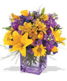 Yellow lilies and purple flowers in a purple cube vase.