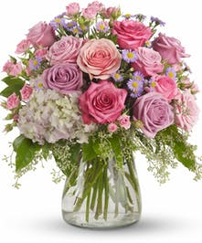 Pink and lavender roses and light pink hydrangea in a clear glass vase.