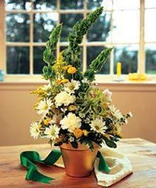 Green, yellow and white flowers in a pot with a green ribbon.