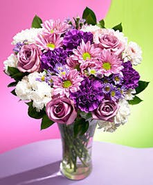 Lavender roses, purple and white carnations, purple asters & chrysanthemums in a clear glass vase.