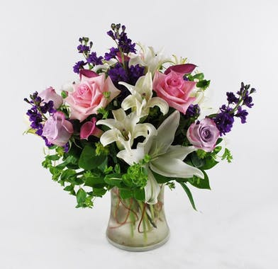 Lilies, roses, stock and greenery in a clear glass vase.