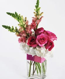 Pink and white roses, snapdragons and hydrangeas in a glass cube vase.