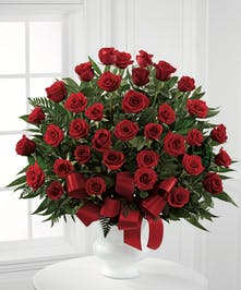 White urn of red roses, suitable for funeral service.