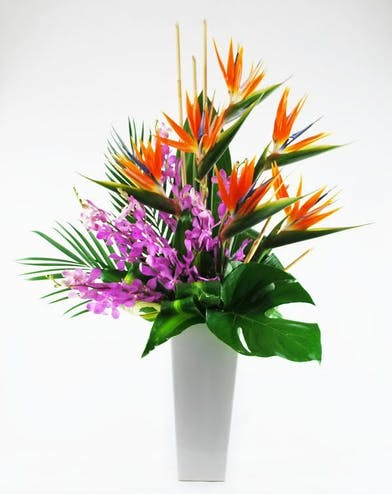 Birds of paradise, orchids and tropical foliage with bamboo accents.