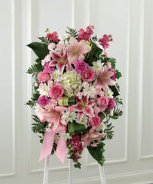 Standing sympathy spray of pale and deep pink flowers including carnations, roses, stock and stargazer lilies.