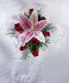 Satin cross pillow adorned with stargazer lilies and sweetheart roses.