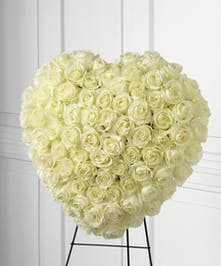 Elegant sympathy tribute of white roses arranged in the shape of a heart.