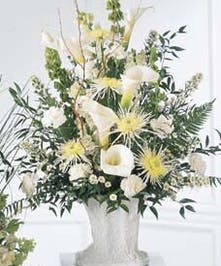 White calla lilies and spider chrysanthemums in a traditional sympathy arrangement.