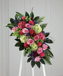 Vibrant sympathy spray of mixed flowers and greenery.