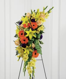 Bright yellow and orange sympathy spray accented with greenery and ribbon.