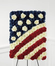 Red, white and blue flowers in the shape of an American flag likeness.