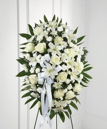 All-white floral standing easel spray with roses, Asiatic lilies, chrysanthemums and mini carnations with greenery.
