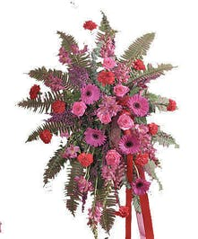 Sympathy spray of pink and red flowers with greenery.