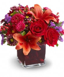 Flowers in hues of red and purple in a wicker basket.
