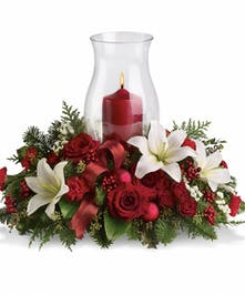Christmas centerpiece of red roses, white lilies, greenery and ornaments with a hurricane candle.