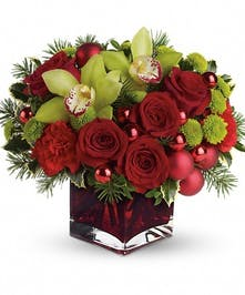 Red cube vase of green and red flowers accented with ornament balls.