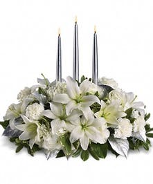 Winter centerpiece of white hydrangea, roses, asiatic lilies, carnations and greenery with three silver taper candles.