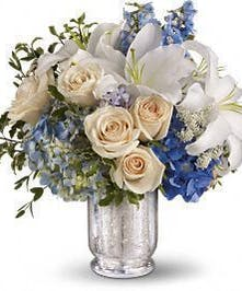 Blue, white and creme flowers in a mercury glass vase