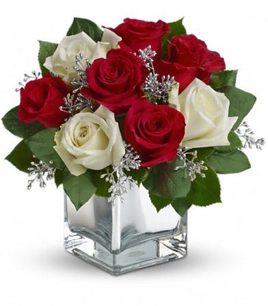Red and white roses in a mirrored cube vase.