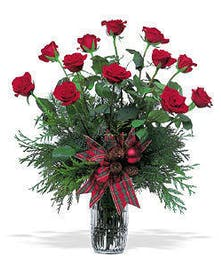 Red roses and winter greenery in a glass vase tied with ribbon.