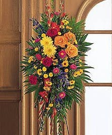 Funeral flower standing easel spray with red, orange and yellow flowers.