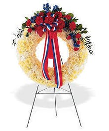 White floral wreath with red and blue flowers accompanied by coordinating ribbon.