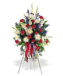 Standing easel spray with red, white and blue flowers and coordinating ribbon.