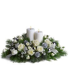 White roses, evergreens, silver pinecones, ornaments, and ribbon with two white pillar candles.
