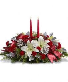 Floral centerpiece of white and red flowers accented with holiday greenery, silver pine cones and red ribbon.