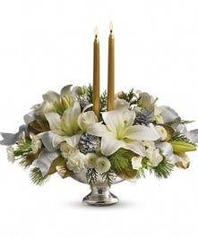 Holiday centerpiece of white flowers, flat cedar, silver pinecones, gold taper candles and silver ribbon.