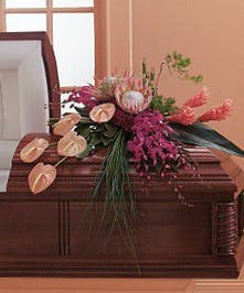 Casket spray of pink and purple tropical flowers.