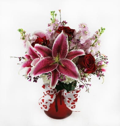 Red and pink flowers in a red vase tied with a white and red bow.