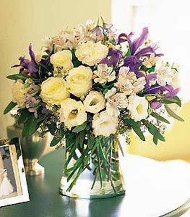White and purple alstroemeria, carnations, delphinium, roses and iris in a clear glass vase.