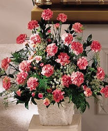 Mache floor arrangement of all pink carnations with ferns and fillers.