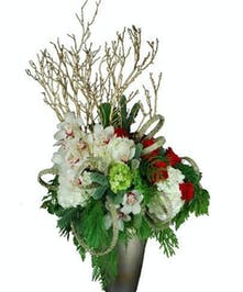 Orchids, roses, hydrangea, and more in a modern vase.